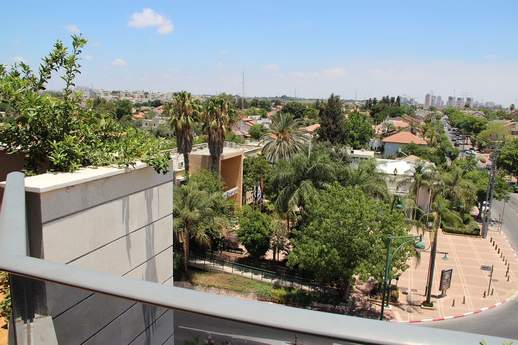 In Ness Ziona bestimmt die Farbe Grün das Stadtbild. Überall wachsen Bäume und laden Grünflächen zum Verweilen ein. Die Hochäuser im Hintergrund gehören zur Nachbargemeinde Be`er Ya`akov